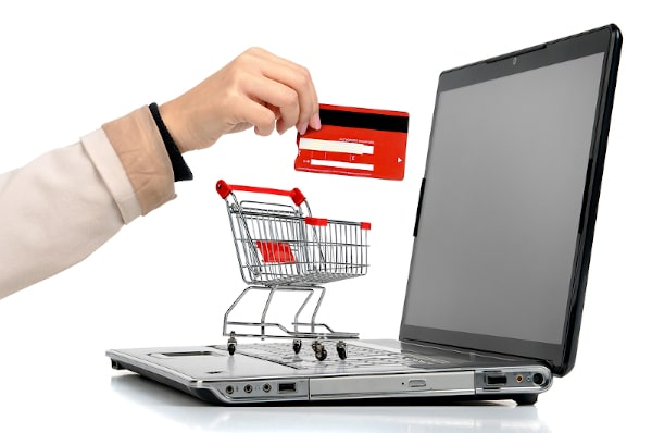 miniature shopping cart on keyboard with credit card ready for checkout